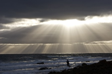Man fishing while the Sun rays find an opening though the  storm clouds.