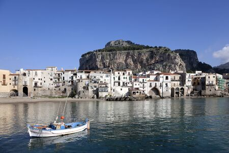 Major tourist attraction an old fishing village. The charm of an rowboat , old buildings, jetting rocks and mountain captured at Cefalu Beach. Located at the town of Cefalu, Sicily, Italy photo