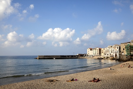 Cefalu Beach, Sicily. People lounging along the beach of Cefalu. In the background the charm of old buildings grace the shoreline  in this old fishing village. Located in the town of  Cefalu, Sicily, Italy photo