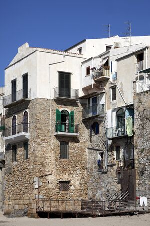 A charming look at an old apartment building located on Cefalu Beach, Sicily