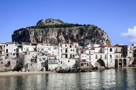 Major tourist attraction an old fishing village. Closer view of the charm of old buildings, jetting rocks and mountain captured at Cefalu Beach. Located at the town of Cefalu, Sicily, Italy photo