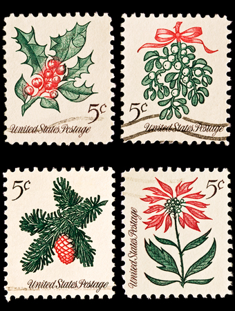 A variety of four Christmas postage stamps  Sprig of conifer, poinsettia, mistletoe and holly