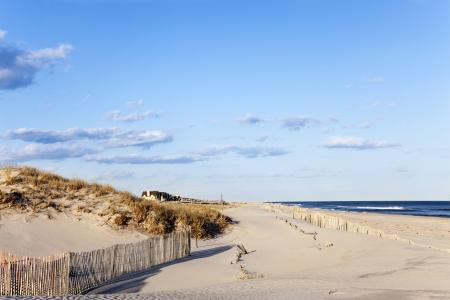 Strand omheining, zand huizen en de oceaan Het hek houdt het zand van achteruit in de oceaan Cupsoque strand, Westhampton, Long Island, New York Stockfoto