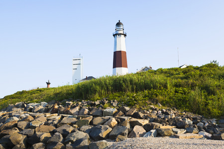 The back of Montauk lighthouse with the rock retainer wall protecting the lighthouse from the Atlantic ocean. Stock Photo