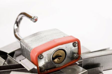 lockout: lock with stapler pins on isolated background   Stock Photo