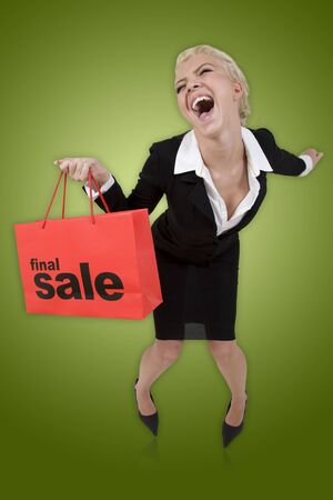 Beautiful blond woman with a red final sale shopping bag on a green isolated background Stock Photo - 3489416