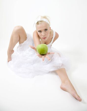 sexy young woman wearing a white dress, holding a green crispy apple in the palm of her hand, on an isolated white background. Stock Photo - 3489397