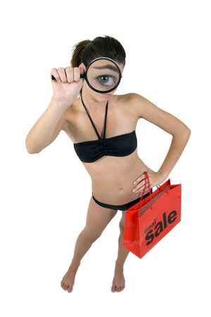 Young, attractive girl in a sexy bikini, magnifying her big blue eye and holding a final sale red shopping bag, on a white isolated background.