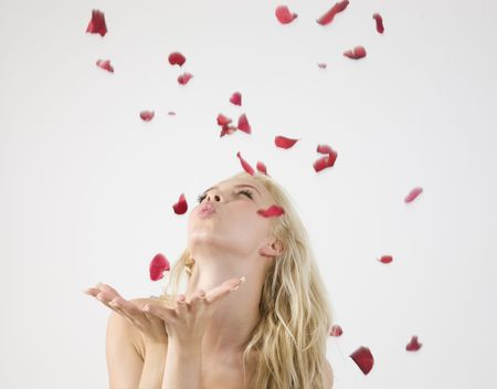 young caucasian lady blowing petals on isolated studio picture Stock Photo