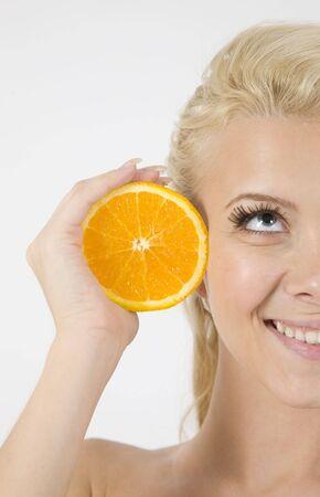 face of model with orange slice on isolated background