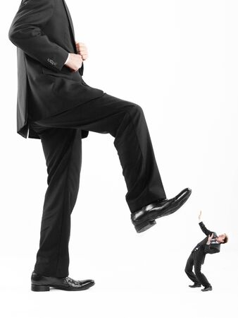 run down: Businessmans foot stepping on tiny businessman Stock Photo