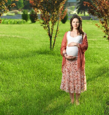 Beautiful pregnant woman in sunny park photo