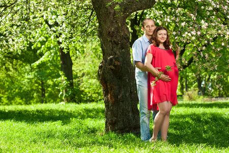 Beautiful pregnant woman in sunny park with her husband photo