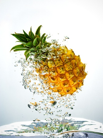 Bubbles forming in blue water after pineapple is dropped into it
