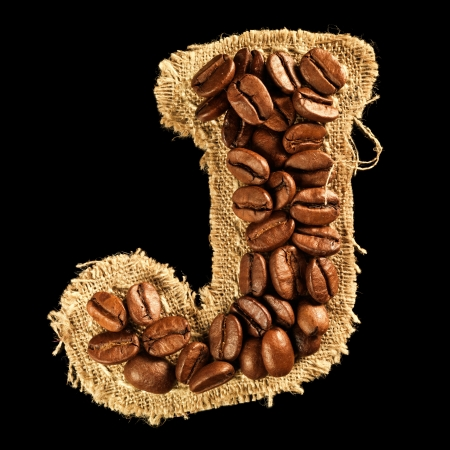 Alphabet from coffee beans on fabric texture isolated on black Stock Photo - 17468167