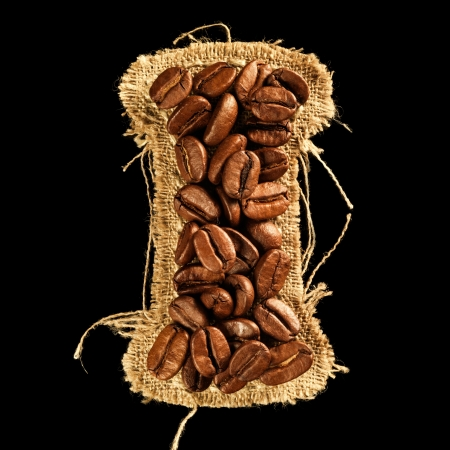 Alphabet from coffee beans on fabric texture isolated on black Stock Photo - 17468127