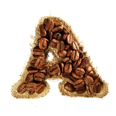 Alphabet from coffee beans on fabric texture isolated on white background photo