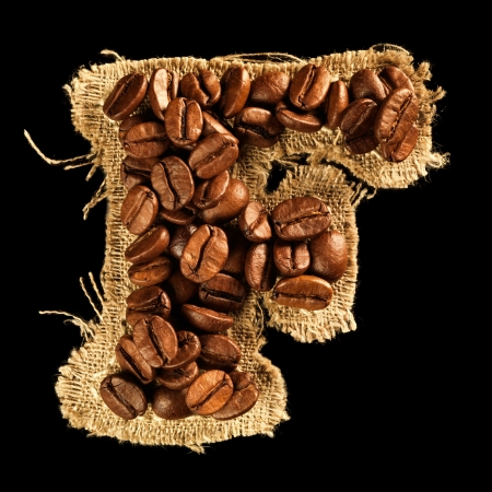 Alphabet from coffee beans on fabric texture isolated on black Stock Photo - 17468159