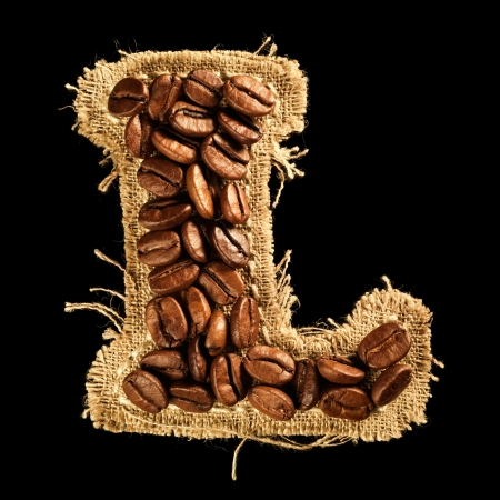 Alphabet from coffee beans on fabric texture isolated on black Stock Photo - 17468155