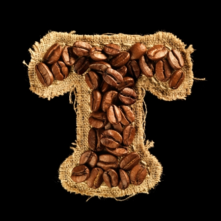 Alphabet from coffee beans on fabric texture isolated on black Stock Photo - 17468158