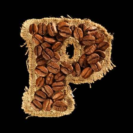 Alphabet from coffee beans on fabric texture isolated on black photo