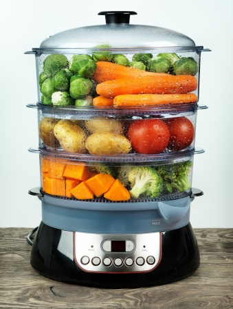 Healthy food in steamer, steam cooker with various vegetables and fruits