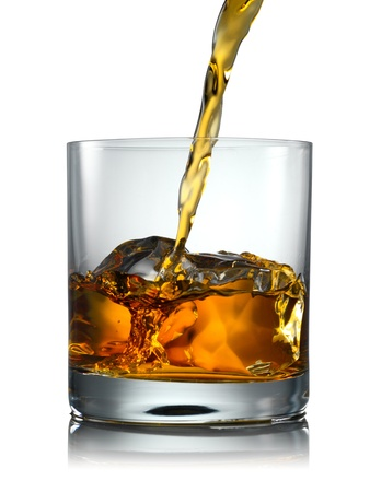 bourbon: Pouring Scotch Whisky in Glass with perfect ice isolated on white