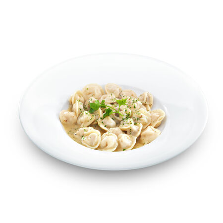 stuffed tortellini: Traditional Russian dumplings with meet or cheese served with parsley on a white round plate. Isolated on white.