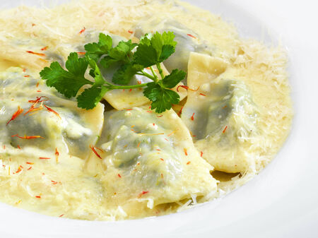 ravioli: Delicious hot healthy vegetarian ravioli with spinach and ricotta under melted parmesan cheese on a round plate isolated on white