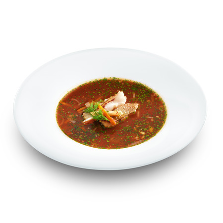 Hot delicious tomato soup with fish and rice served with leek and parsley in a white bowl. Isolated on white. photo