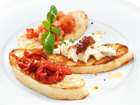 Assorted bruschetta with salmon, air-dry tomatoes or goat cheese served with the basil leaf on a round white plate isolated on white. photo
