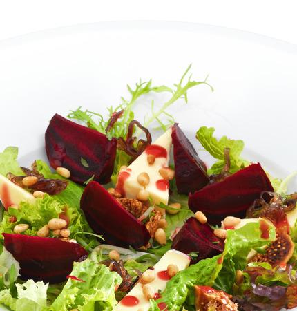 queso de cabra: Ensalada gourmet vegetariana fresca con remolacha asada y queso servido en un plato redondo blanco. Aislado en blanco.