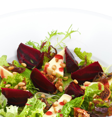 goat cheese: Fresh vegetarian gourmet salad with baked beetroot and cheese served on a white round plate. Isolated on white.