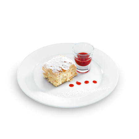 Delicious and yummy Napoleon cake with confectioners sugar and  berry topping on a round plate isolated on white photo
