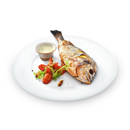 Grilled healthy dorado fish with vegetables on a round plate isolated on white photo
