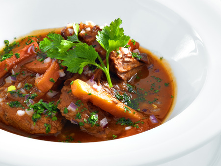 Rich hot hungarian beef goulash with traditional topping served on a round white plate  Isolated on white  photo