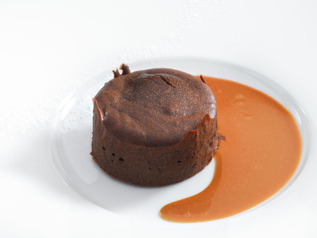 molted: Delicious chocolate fondant with caramel sauce served on a white round plate  Isolated on white  Stock Photo