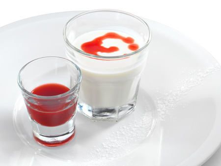 Smooth and creamy panna cotta with strawberry and raspberry sauce in a small glass isolated on white. photo