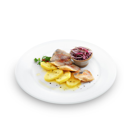 Healthy salted herring with baked potatoes, onion and fennel is served on a white plate. Isolated on white.  photo