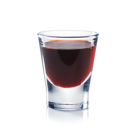 Red berries liqueur is the shot glass isolated on white  Bar and restaurant concept