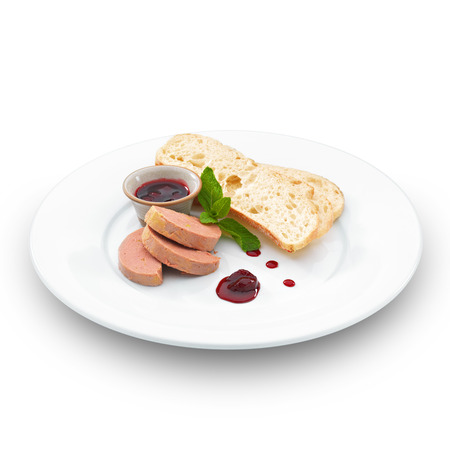 Gourmet fresh foie gras pate served with ciabatta, berry sauce and basil leaf. Isolated on white. photo