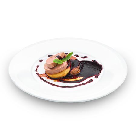 Gourmet foie gras geserveerd met rode bessensaus en gedecoreerd met basilicum blad. Geïsoleerd op wit.