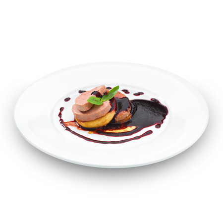 Gourmet foie gras served with red berry sauce and decorated with basil leaf. Isolated on white.