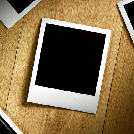 Polaroid fiilm vintage empty photo card on wooden background photo