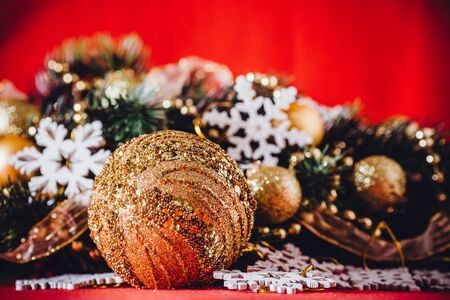 space for copy: Christmas card with fir tree branch decorated with golden baubles, garlands and vintage snowflakes on a red background with copy space for your text