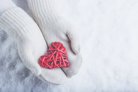 entwined: Female hands in white knitted mittens with a entwined vintage romantic red heart on a winter snow background. Love and St. Valentine cozy concept.