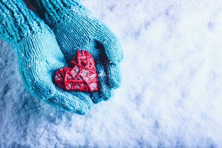 Woman hands in light teal knitted mittens are holding a beautiful entwined vintage romantic red heart in a snow background.