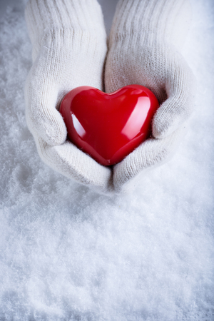 hands holding heart: Female hands in white knitted mittens with a glossy red heart on a snow winter background. Love and St. Valentine cozy concept.