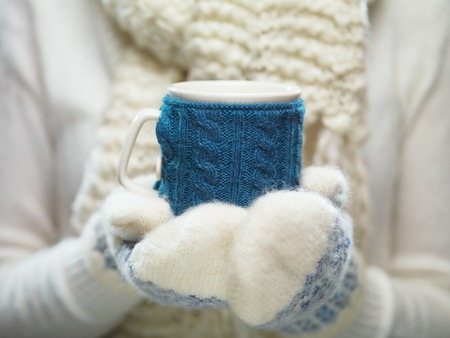Ženské ruce drží pletený zimní hrnek zblízka. Žena ruce v bílé a modré palčáky drží útulné pletené šálek s horkým kakaem, čajem nebo kávou. Zimní a vánoční časový koncept.