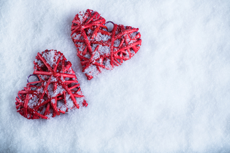 falling in love: Two beautiful romantic vintage red hearts together on a white snow winter background. Love and St. Valentines Day concept